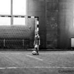 モノクロ男の子がサカーゴールの前にいる画像