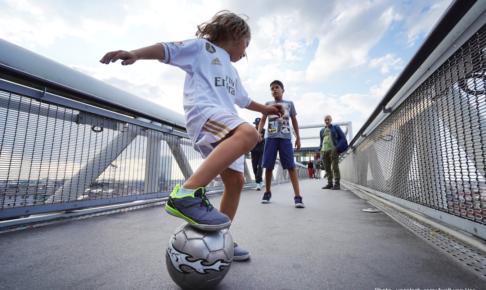 子どもが足でボールを押さえている画像