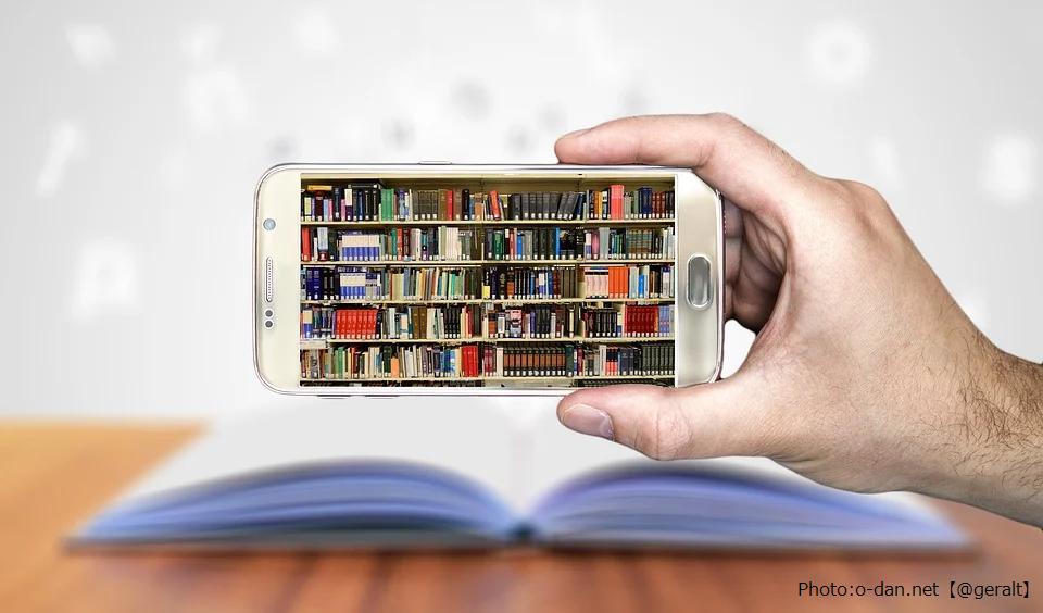 スマートフォンに本棚が映し出されている画像